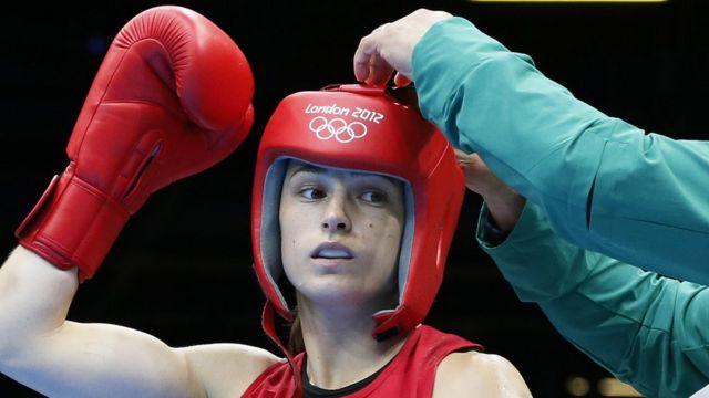 Una mujer boxeadora con el protector en su cabeza.