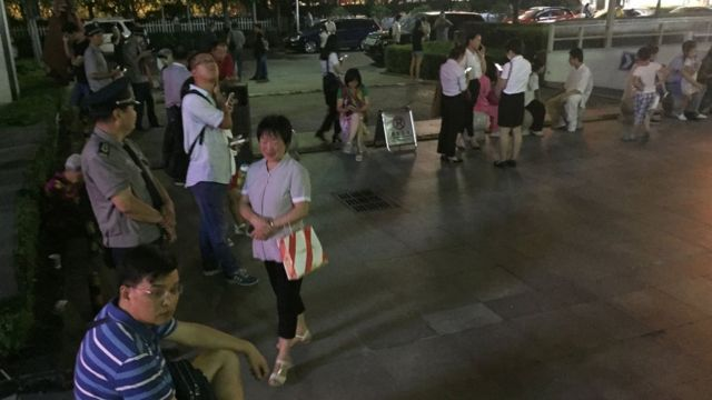 Residents gather outside buildings in Xian, China, on 8 August 2017