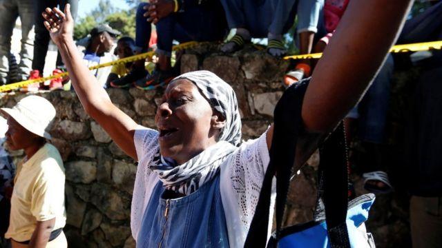Una mujer reacciona con una expresión de dolor en el lugar donde se incendió el orfanato.