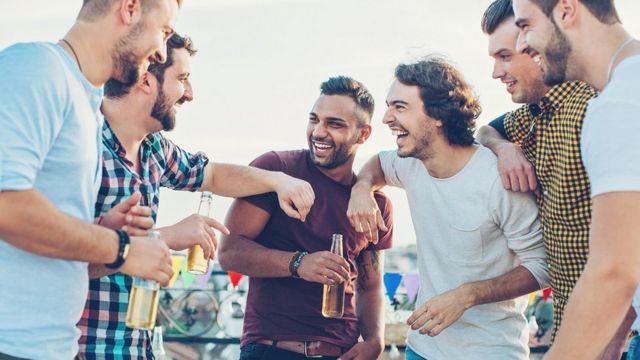 Grupo de jovens com bebidas e sorrindo