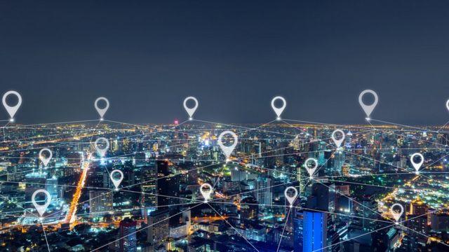 Cidade com vários prédios iluminados durante a noite e símbolos de localização ilustrados e sobrepostos