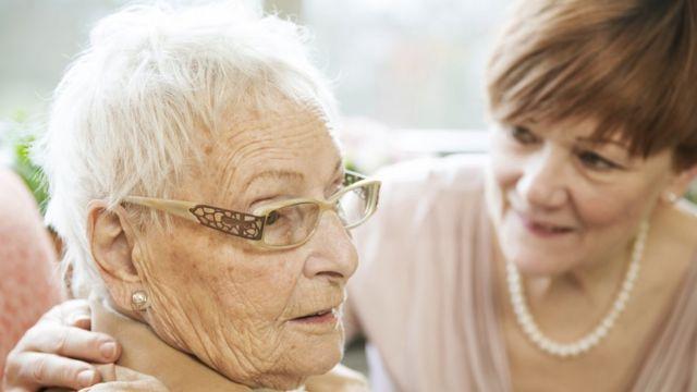 Una mujer anciana con demencia, acompañada por una mujer más joven