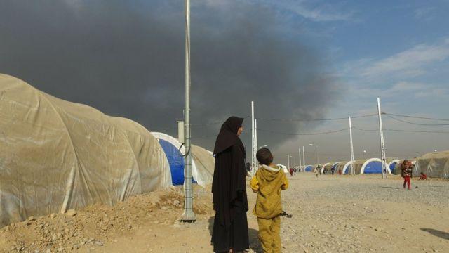 سحب دخان تتصاعد من بئر نفط تم تفجيره غير بعيد عن مخيم أربيل للنازحين