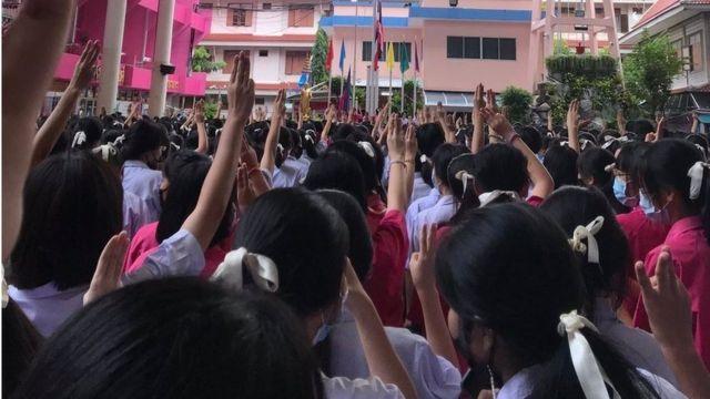 เด็กนักเรียนชูสามนิ้ว