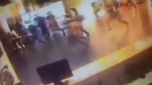 CCTV shows people running in the terminal as an explosion hits.