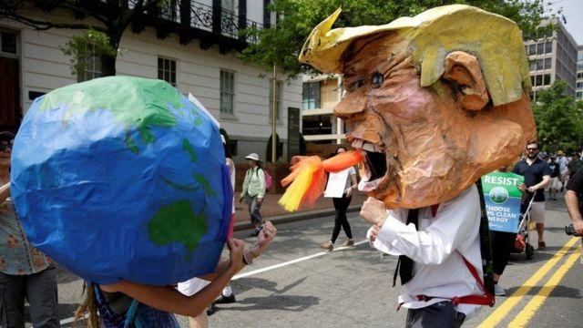 Personas con disfraces de la Tierra y Trump peleando.