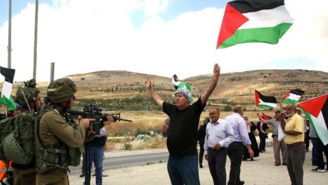 Un manifestante palestino de Cisjordania protesta frente a soldados israelíes.
