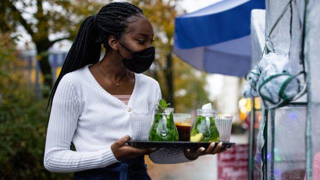 Máscara camarera sosteniendo la bandeja con bebidas.