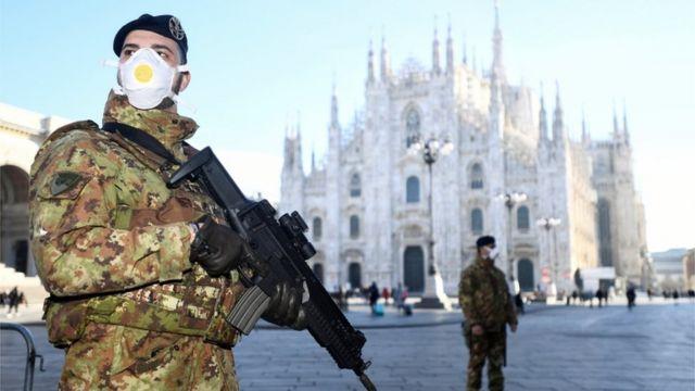 ทหารอิตาลีพร้อมอาวุธ สวมหน้ากาก ยืนอยู่ที่ด้านนอกโบสถ์ในเมืองมิลา 24 ก.พ. 2020
