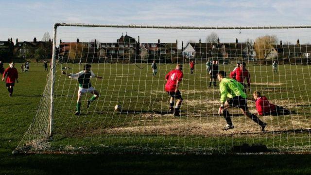 Partida de futebol em parque de Londres