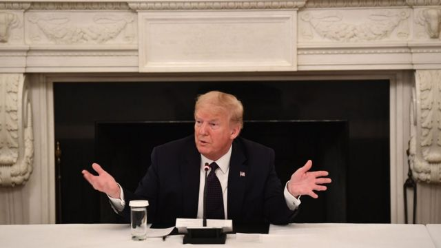 Trump fala e gesticula sentado em sala de reunião na Casa Branca