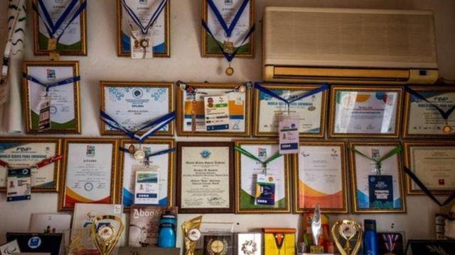 تصویری از مدالها و جوایز الحسین روی دیوار خانهاش در آتن