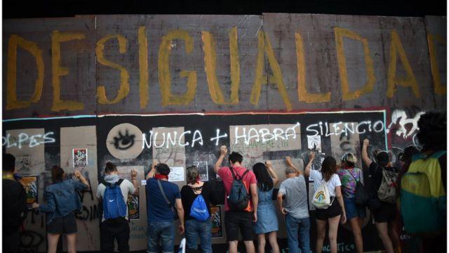 """Protesta en Chile bajo una pintada que lee """"Desigualdad""""."""