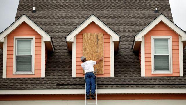 Un hombre coloca una protección de madera en la ventana de su casa en Carolina del Sur.