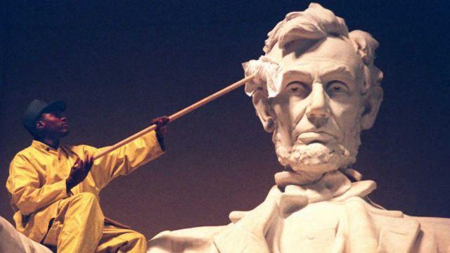 Homem limpa estátua de Abraham Lincoln