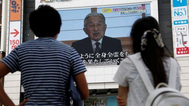 Japoneses observam a mensagem do imperador em telas nas ruas