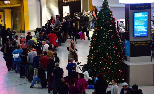 A queue of passengers next to a Christmas tree