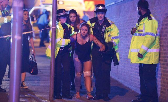 Mujer herida camina acompañada de varios agentes de policía