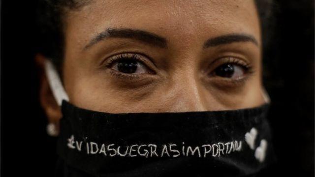 Mulher com máscara em que se lê vidas negras importam