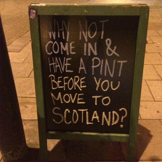 Letrero de pub con la frase ¿Por qué no entras y te tomas una cerveza antes de que te mudes a Escocia?