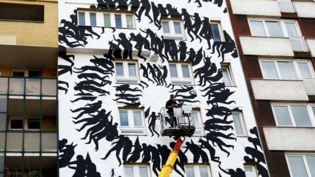 Художник Девід де ла Мано малює на житловому будинку поблизу музею
