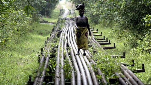 امرأة تسير وفق أنابيب نقل النفط في نيجيريا