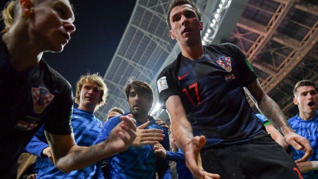 Croatian players helping photographer Yuri Cortez to his feet