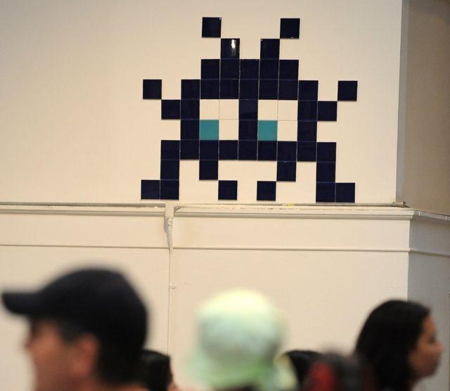Работа Захватчика, французского уличного художника, как экспонат на выставке в Лос-Анджелесе