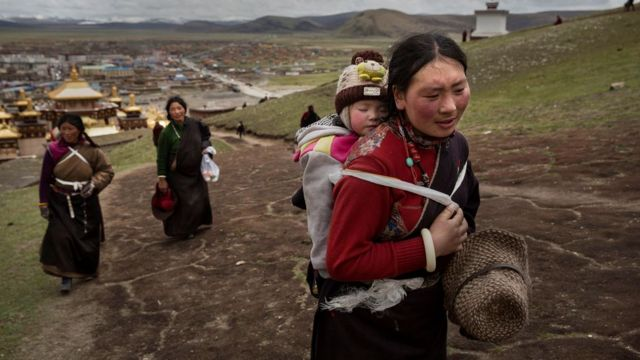 Mulher tibetana carregando bebê nas costas