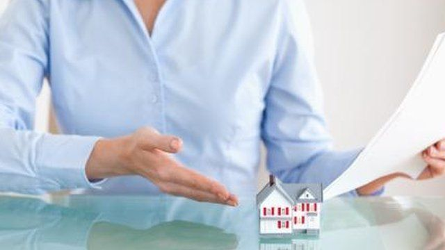 Woman pointing to a model house
