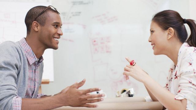 A man and a woman smiling face to face in an office