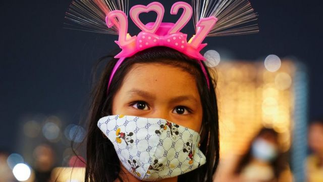 "A young woman wearing a protective facce mask and ""2021"" head band looks on at a shopping mall as The New Year countdown celebrations in Bangkok"