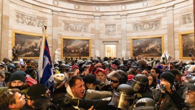 警察与闯入国会山的暴徒对峙。