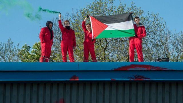 """نشطاء من مجموعة """"حراك من أجل فلسطين"""" في بريطانيا على سطح بناية مصنع للطائرات المقاتلة المسيرة المملوك لشركة إسرائيلية في ليستر، بريطانيا"""