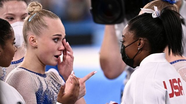 Russian Angelina Melnikova (left) receives congratulations from American Simone Biles after Russia won the final of the artistic gymnastics women's team during the Tokyo 2020 Olympic Games.