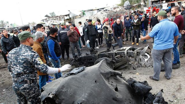 Iraqi police and bystanders look at the wreckage of a vehicle destroyed in a suicide car bomb attack in Sadr City, Baghdad (2 January 2017)