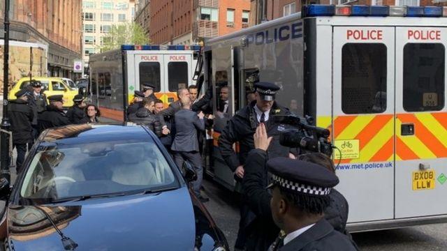 အီကွေဒေါသံရုံးရှေ့မှာ အသင့်စောင့်နေတဲ့ ရဲကားထဲ ဂျူလီယန်အာဆန်းကို ဆွဲသွင်းခေါ်သွားခဲ့။