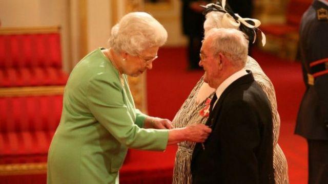 Casal de idosos em traje de gala recebe condecoração da rainha da Inglaterra