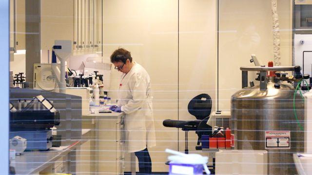 Pesquisadora usando luvas e jaleco analisa informações em um laboratório
