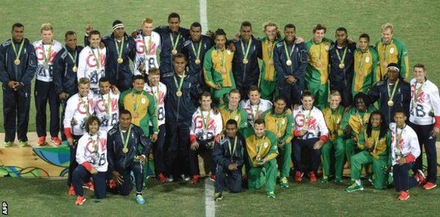 メダルを獲得したフィジー、英国、南アフリカの選手たちが入り交じり写真撮影のためにポーズした