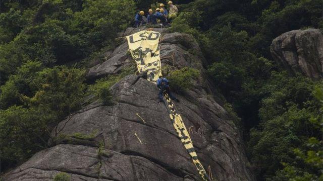 ビーコンヒルに掲げられた民主化を訴える垂れ幕を撤去する作業員
