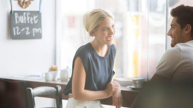 Una pareja charlando y ríendo en un café