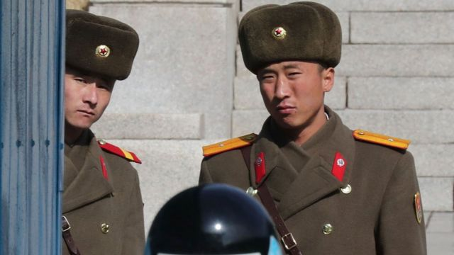 North Korean soldiers look on as a South Korea soldier (bottom) stands guard at the joint security area during a visit of Australian Foreign Minister Julie Bishop at the truce village of Panmunjom in the Demilitarized zone (DMZ) dividing the two Koreas on 18 February 2017.