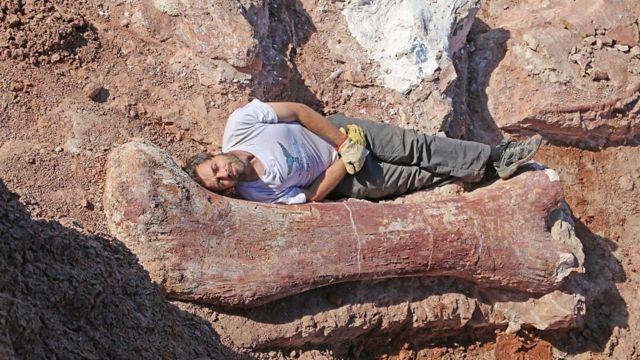 Diego Pol acostado al lado de un hueso de dinosaurio.