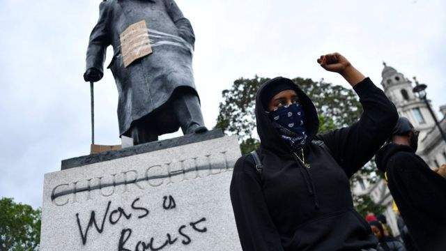 A protester stands in front of the Churchill statue