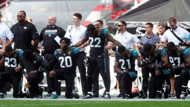 Members of the Jacksonville Jaguars kneel and lock arms in protest during the national anthem before the NFL International Series match at Wembley Stadium in London.