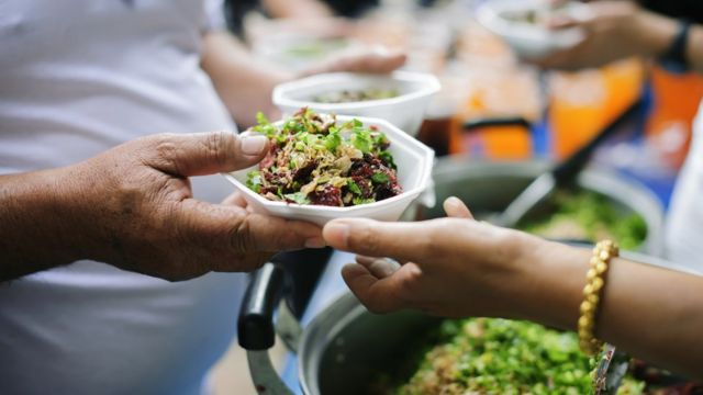 Pessoa recebendo prato de comida