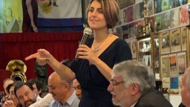 Em pé em mesa de restaurante, Manuela d'Ávila fala no microfone