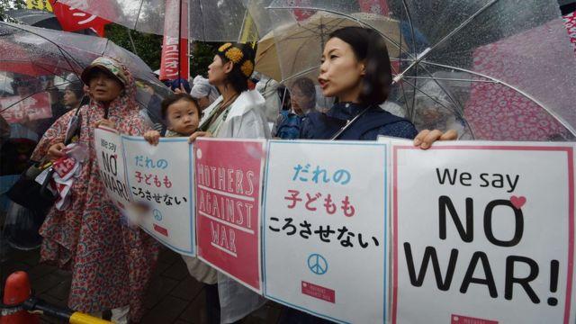 子ども連れの若い母親も雨の中、傘をさして反対デモに参加した(17日)