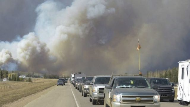 Plumes of smoke rise in the air, as people flee the wildfire in their cars in Fort McMurray